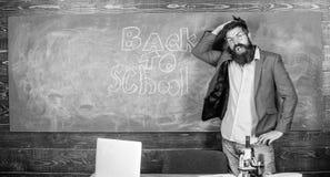 Nauczyciel lub pedagog witamy uczni podczas gdy stojaki zbliżają chalkboard z inskrypcją z powrotem szkoła Zaprasza szkoła obraz stock