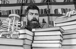 Nauczyciel lub uczeń z brodą siedzimy przy stołem z książkami, defocused bibliophile pojęcie Mężczyzna na zmieszanej twarzy pośro fotografia stock