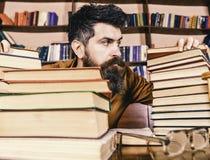 Nauczyciel lub uczeń z brodą siedzimy przy stołem z szkłami, defocused bibliophile pojęcie Mężczyzna na surowej twarzy pośrodku fotografia stock