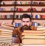 Nauczyciel lub uczeń z brodą siedzimy przy stołem z szkłami, defocused Mężczyzna na surowej twarzy między stosami książki, podcza obraz royalty free