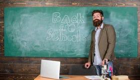 Nauczyciel namiętna akcydensowa zdolność dosięga out uczni Nauczyciel blisko chalkboard chwytów kredy pisze inskrypci z powrotem  obrazy stock