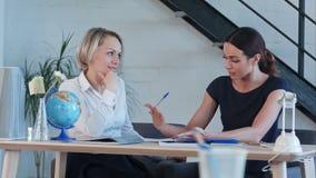 Nauczyciel opowiada each inny przy biurkiem zdjęcie wideo