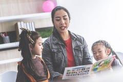 Nauczyciel opowieści czytelnicza książka dziecinów ucznie zdjęcie stock