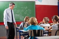 Nauczyciel Patrzeje uczni Siedzi W sala lekcyjnej Zdjęcie Royalty Free