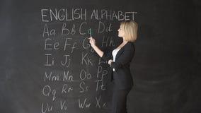 Nauczyciel pisze liście abecadło na blackboard z kredą Edukacja w szkoły podstawowej pojęciu zdjęcie wideo