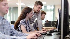 Nauczyciel Pomaga Żeńskiej szkoły średniej Studenckiemu działaniu W komputer klasie zbiory