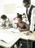 Nauczyciel pomaga afroamerykańskiej uczennicy w sala lekcyjnej zdjęcia royalty free
