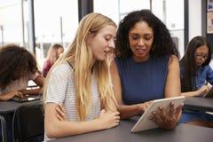 Nauczyciel pomaga blondynki nastoletniej uczennicy z pastylka komputerem Zdjęcie Stock