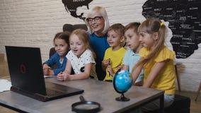 Nauczyciel pomaga caucasian dzieci przy komputerowym terminal w szkole podstawowej Uśmiechnięci szkoła dzieciaki używa komputer z zdjęcie wideo