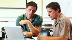 Nauczyciel pomaga dojrzałego ucznia w komputer klasie na laptopie zbiory