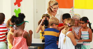 Nauczyciel pomaga dzieciaków w laboratorium zdjęcie wideo