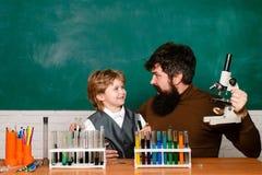 Nauczyciel pomaga m?odej ch?opiec z lekcj? Rozochocona uśmiechnięta chłopiec i nauczyciel ma zabawę przeciw błękit ścianie rodzic fotografia royalty free