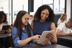 Nauczyciel pomaga nastoletniej uczennicy z pastylka komputerem Obrazy Stock