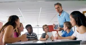 Nauczyciel pomaga schoolkids na cyfrowej pastylce 4k zbiory wideo