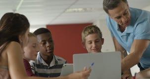 Nauczyciel pomaga schoolkids na laptopie 4k zbiory