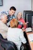 Nauczyciel Pomaga Starszych ludzi W Używać komputer Przy sala lekcyjną Zdjęcie Stock