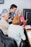 Nauczyciel Pomaga Starszych uczni W Używać komputer Przy sala lekcyjną Obraz Stock
