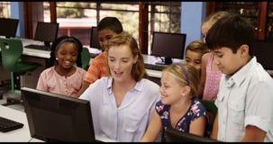 Nauczyciel pomaga szkoła dzieciaki na osobistym komputerze w sala lekcyjnej zbiory