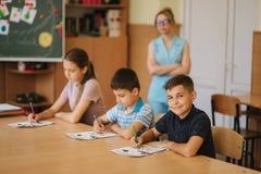 Nauczyciel pomaga szko?a ?artuje pisa? tescie w sali lekcyjnej edukacja, szkoła podstawowa, uczenie i ludzie pojęć, obrazy royalty free
