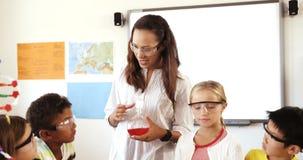 Nauczyciel pomaga szkolnych dzieciaków w robić eksperymentowi w sala lekcyjnej zbiory