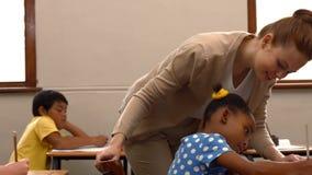 Nauczyciel pomaga troszkę dziewczyny podczas klasy zbiory