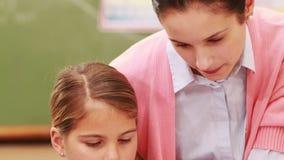 Nauczyciel pomaga troszkę dziewczyny podczas klasy zdjęcie wideo