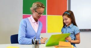 Nauczyciel pomaga uczennica z jej pracą domową w sala lekcyjnej zbiory