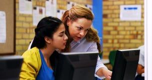 Nauczyciel pomaga uczennicy w komputer klasie zbiory
