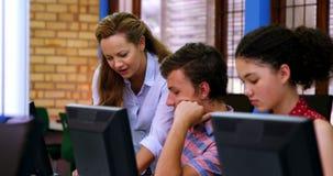Nauczyciel pomaga uczni w komputer klasie zdjęcie wideo