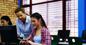 Nauczyciel pomaga uczni w komputer klasie zbiory wideo