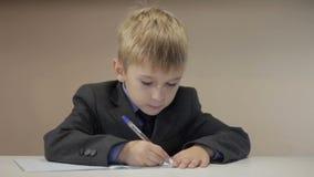 Nauczyciel pomocy chłopiec pisze zbiory