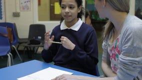Nauczyciel Pracuje Z Żeńskim uczniem Przy biurkiem zdjęcie wideo