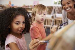 Nauczyciel Przy Montessori szkoły Pomaga dziećmi w sztuki klasie zdjęcia royalty free