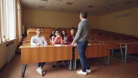 Nauczyciel przychodzi sala lekcyjna i zaczyna opowiadać ucznie, wykład zaczyna, ucznie biorą taxtbooks i zbiory