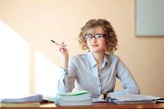 Nauczyciel siedzi przy biurkiem w sala lekcyjnej i sprawdza notatnika Fotografia Royalty Free