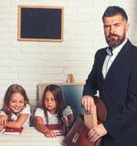 Nauczyciel stawia ksi??k? teczka przy klas? z dzieciakami zdjęcia royalty free