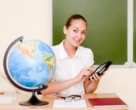 Nauczyciel trzyma pastylkę komputerowa przy sala lekcyjną Zdjęcie Royalty Free