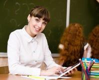 Nauczyciel trzyma pastylkę komputerowa przy sala lekcyjną Fotografia Stock