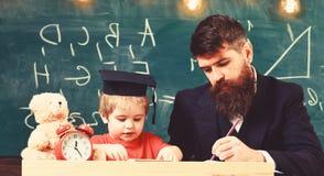 Nauczyciel w formalnej odzie?y i uczniu w mortarboard w sala lekcyjnej, chalkboard na tle Ojciec sprawdza prac? domow?, pomoce zdjęcia royalty free