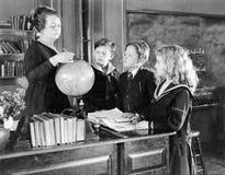 Nauczyciel w sala lekcyjnej z trzy uczniami wskazuje kula ziemska (Wszystkie persons przedstawiający no są długiego utrzymania i  Obrazy Stock