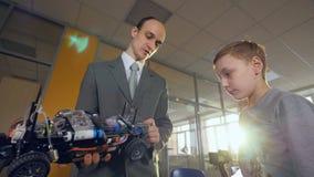 Nauczyciel wyjaśnia chłopiec jak samochód pracuje zbiory