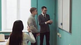 Nauczyciel wyjaśnia coś na whiteboard ucznie zbiory wideo