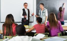 Nauczyciel wyjaśnia matematykę blisko chalkboard Obraz Royalty Free