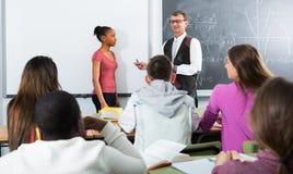 Nauczyciel wyjaśnia matematykę blisko chalkboard Obrazy Royalty Free