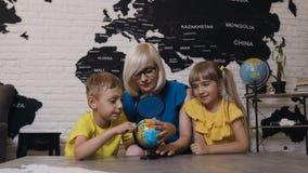Nauczyciel z dwa dzieciakami w geografii klasie patrzeje kulę ziemską Śliczna chłopiec, dziewczyna i nauczyciel patrzeje kuli zie zdjęcie wideo