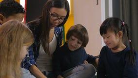 Nauczyciel z dzieciakami czyta książkę w dziecinu zbiory