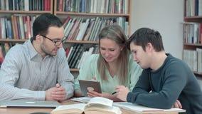 Nauczyciel z grupą ucznie pracuje na cyfrowej pastylce w bibliotece zdjęcie wideo