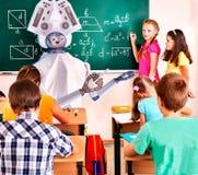 Nauczyciela ai robot z dziecko w wieku szkolnym w szkolnej klasy blackboard obraz royalty free