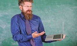 Nauczyciela brodaty mężczyzna wprawiać w zakłopotanie pracę z nowożytnym laptopu chalkboard tłem Modnisia wyrażenia nauczyciele w zdjęcie royalty free