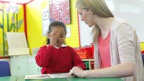 Nauczyciela czytanie Z Żeńskim uczniem Przy biurkiem zdjęcie wideo